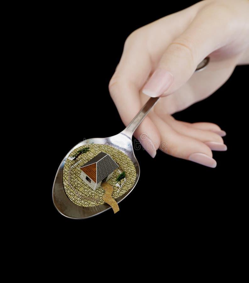 Frauenhand, die Löffel mit PapierImmobiliengeschäftskonzeptfoto des hauses hält stockfotografie