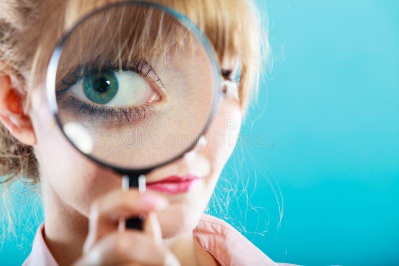 Frauenhand, die Lupe auf Auge hält lizenzfreie stockbilder