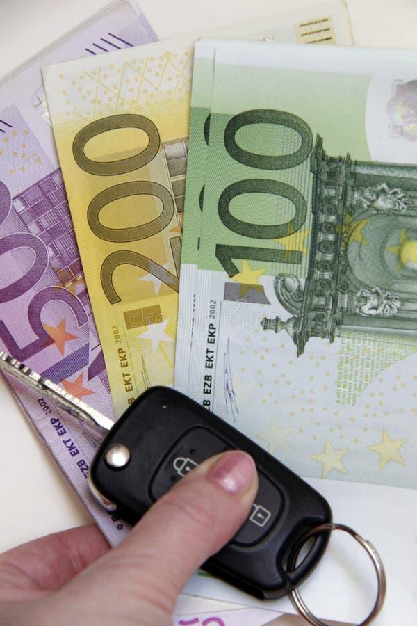 Frauenhand, die Luxusneuwagen-Schlüssel und Euro-Banknoten hält lizenzfreie stockbilder
