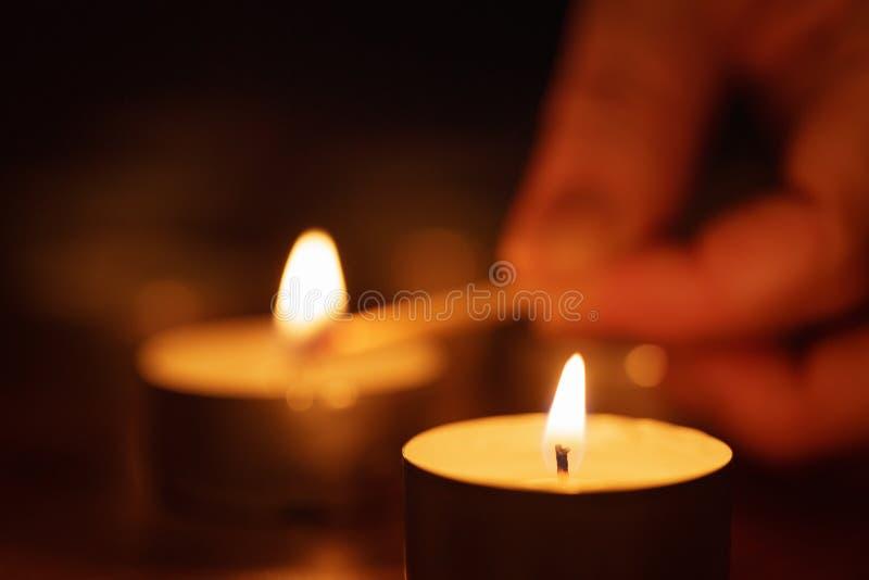 Frauenhand, die nahes hohes der Kerze einstellt lizenzfreie stockfotos