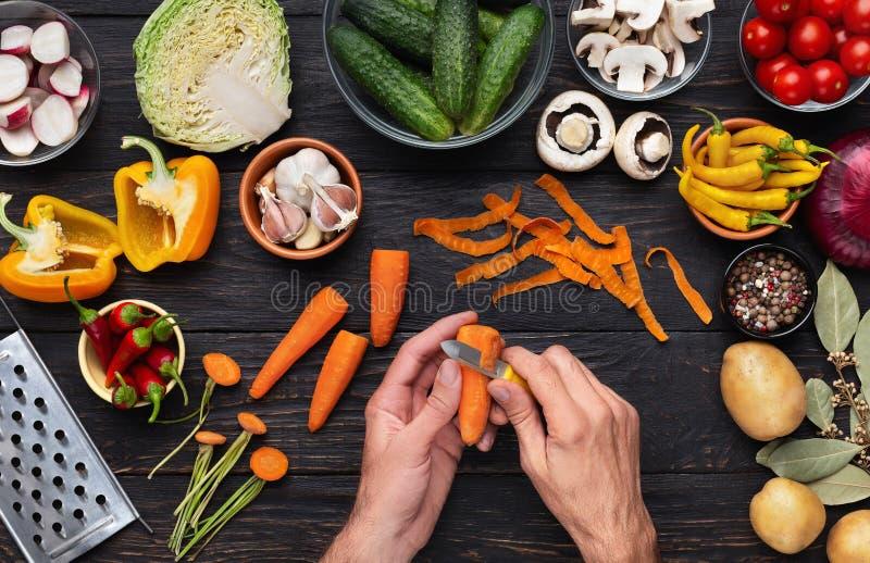 Frauenhand, die orange Karotte mit Schäler abzieht stockbilder