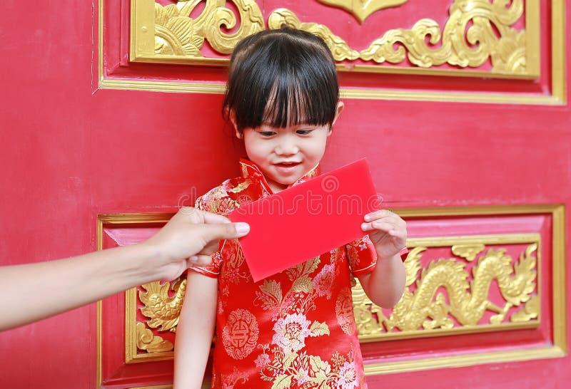 Frauenhand, die rotem Paket Währungsgeschenk für nettes kleines Mädchen am chinesischen Tempel in Bangkok, Thailand gibt Chinesis lizenzfreies stockfoto