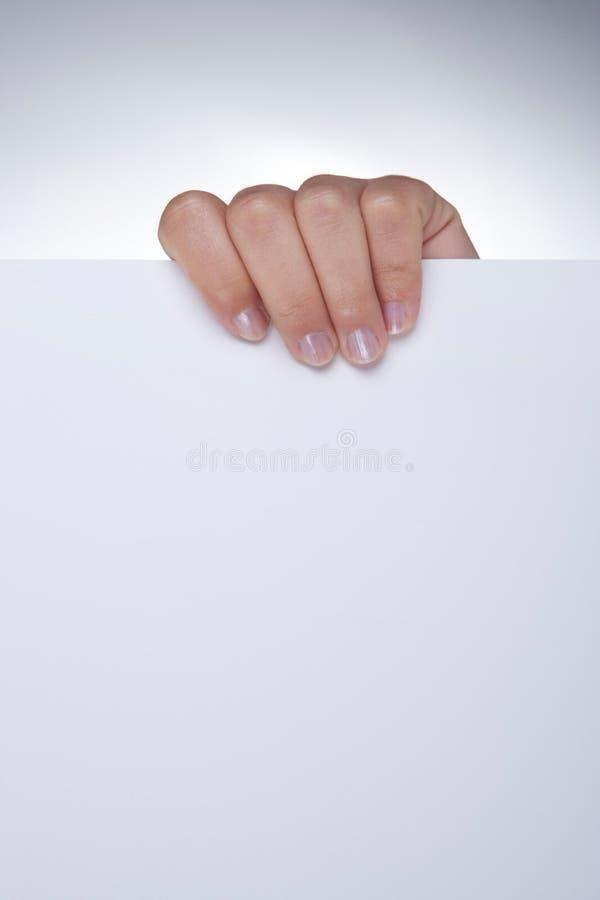 Frauenhand, die weißes unbelegtes Papier anhält stockbilder