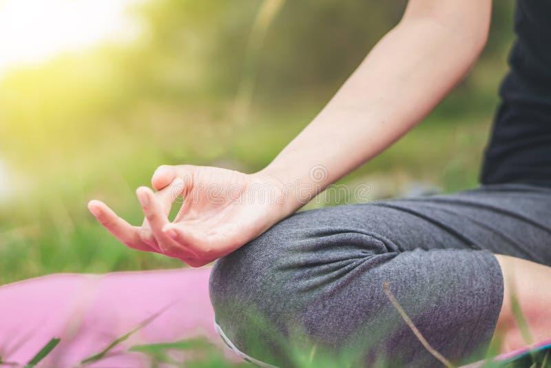 Frauenhand, die Yoga tut und auf grünem Gras meditiert stockbild