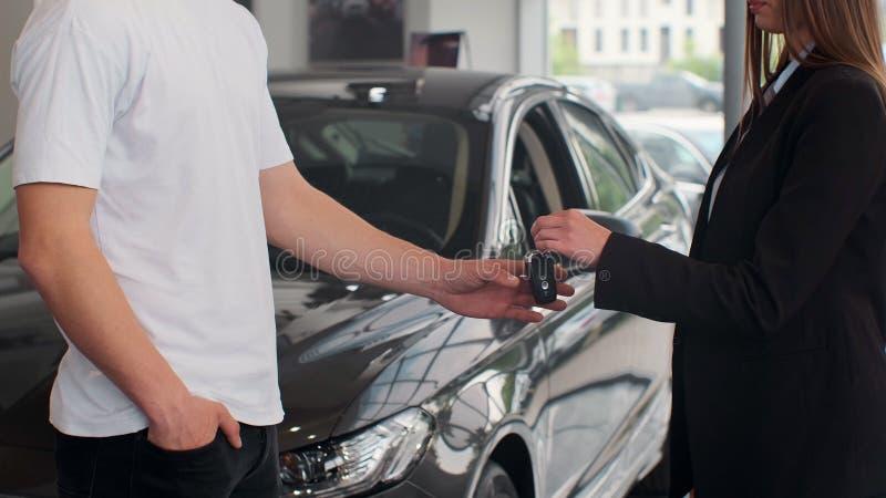 Frauenhand gibt Schlüssel eines Autos, um Hand im Auto-Vertragshändler-Abschluss oben zu bemannen Unerkannter Selbstverkäufer und stockfoto