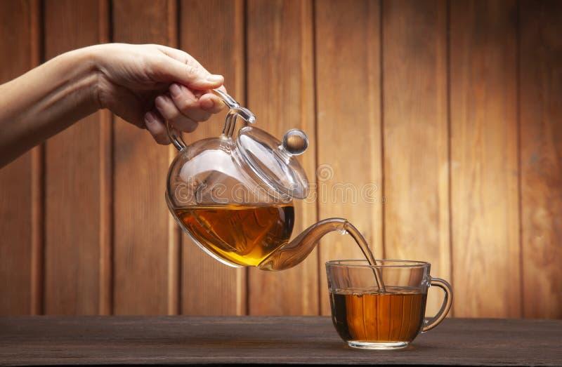 Frauenhand goss Tasse Tee auf einem Holztisch von einer Teekanne stockbild