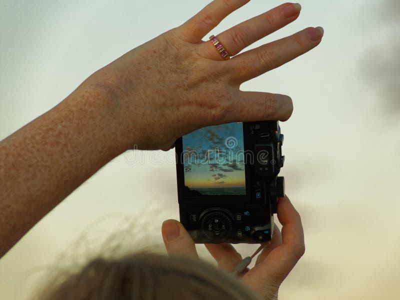 Frauenhand hält Kamera mit Sonnenunterganghimmel auf Schirm stockfotografie