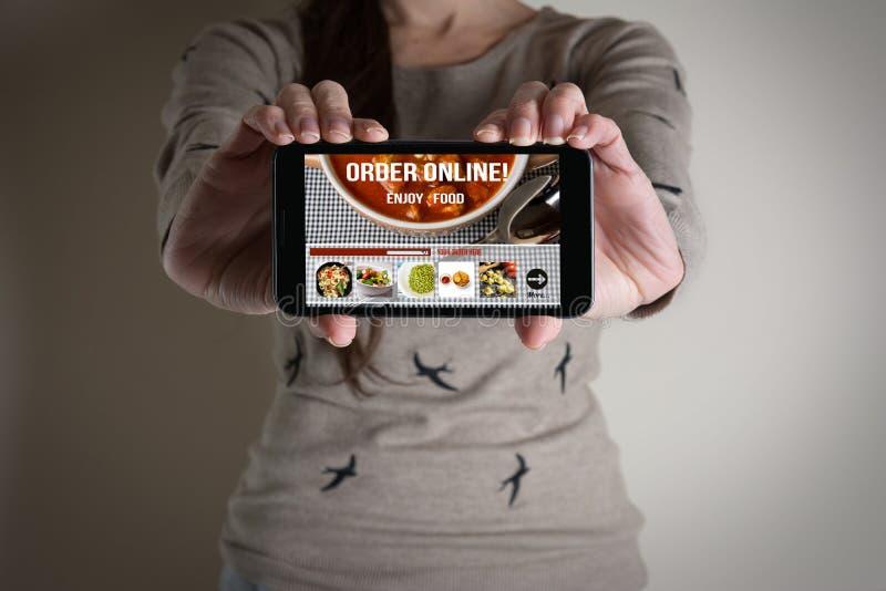 Frauenhand halten beweglich mit dem Bestellungslebensmittel on-line lizenzfreie stockfotos