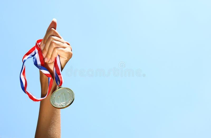 Frauenhand hob an und hielt Goldmedaille gegen skyl Preis- und Siegkonzept Selektiver Fokus Retro- Art-Bild stockbilder