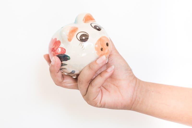 Frauenhand legt eine Münze in einem Sparschwein stockbild