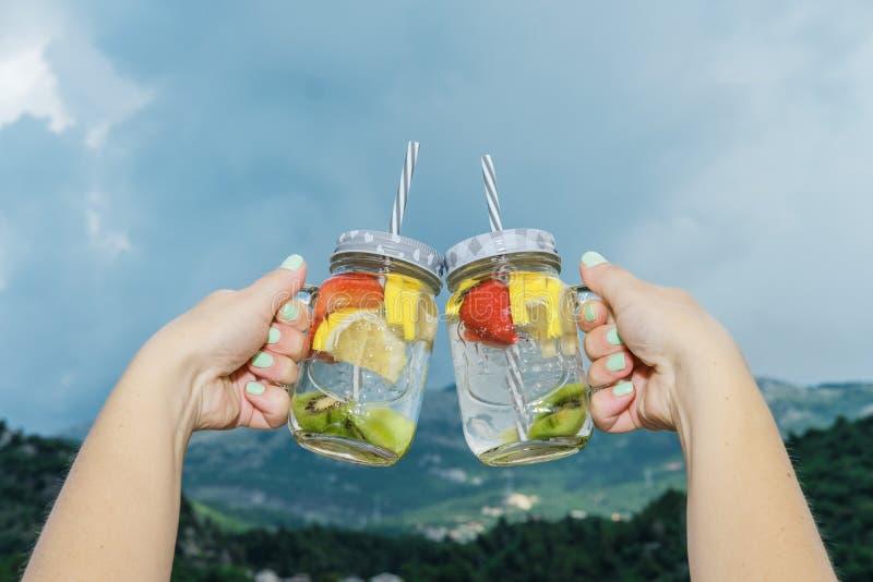 Frauenhand mit Fruchtwasser mit Zitrone und Erdbeeren in einem gla lizenzfreies stockbild