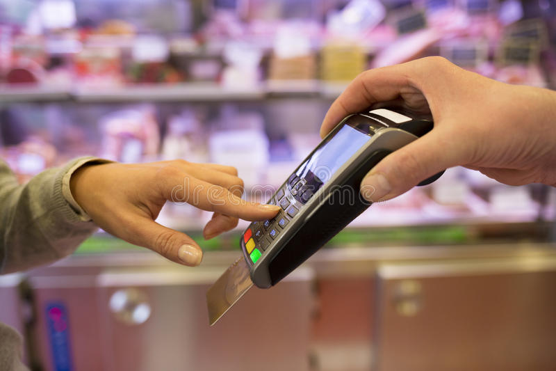 Frauenhand mit Kreditkarteschlag durch Anschluss für Verkauf, herein stockfotografie