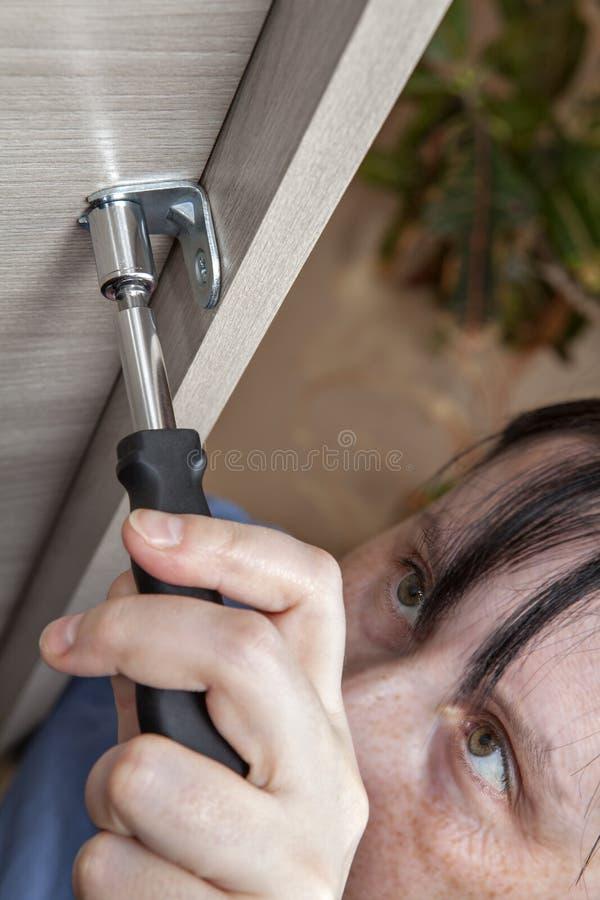 Frauenhand mit Nussspinnerfahrer ziehen Nuss, Nahaufnahme fest lizenzfreies stockbild