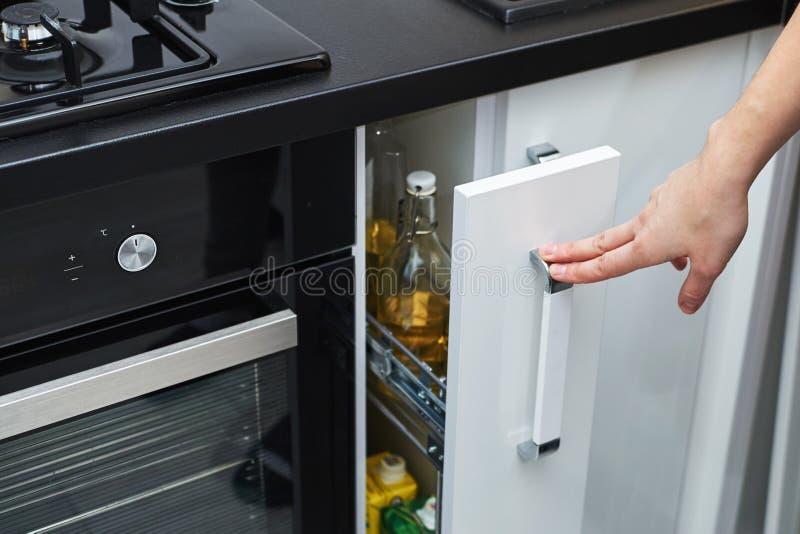 Frauenhand offen ein Küchenspeicherkabinett im modernen Innenraum lizenzfreie stockfotografie