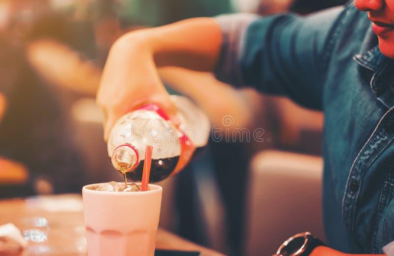 Frauenhandgriff gießen Kolabaum im Glas Kolabaum spritzend mit Eis auf Holztischcaféhintergrund lizenzfreies stockfoto