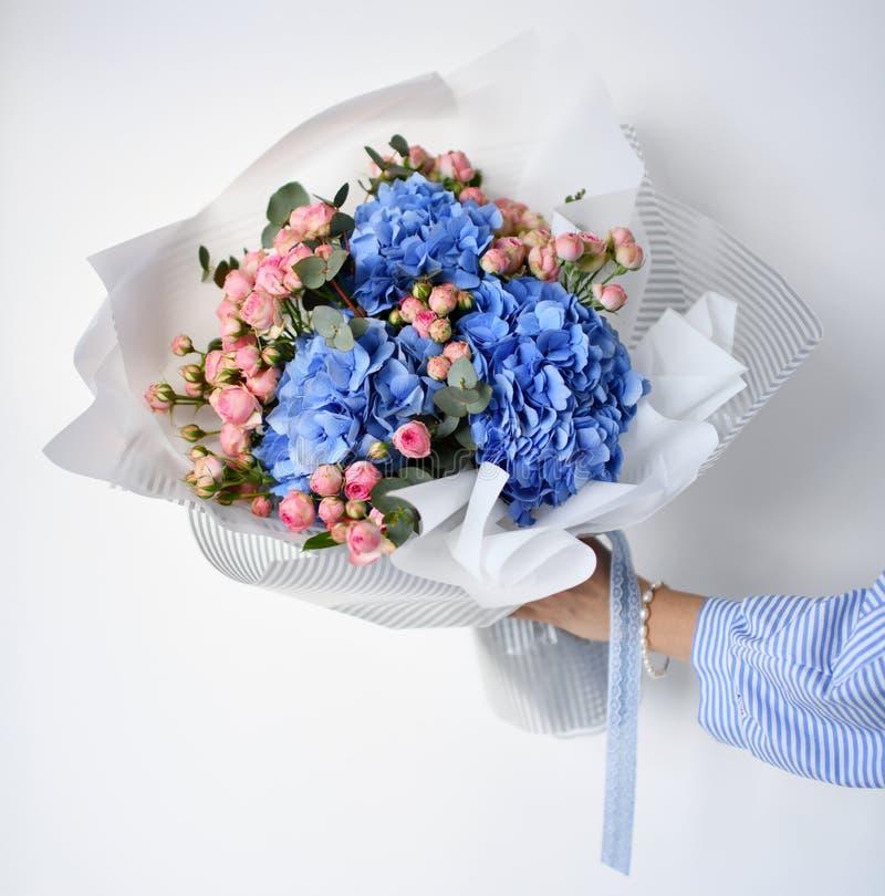 Frauenhandgriffblumenstrauß von blauen Hortensieblumen und von rosa Rosen lizenzfreies stockbild