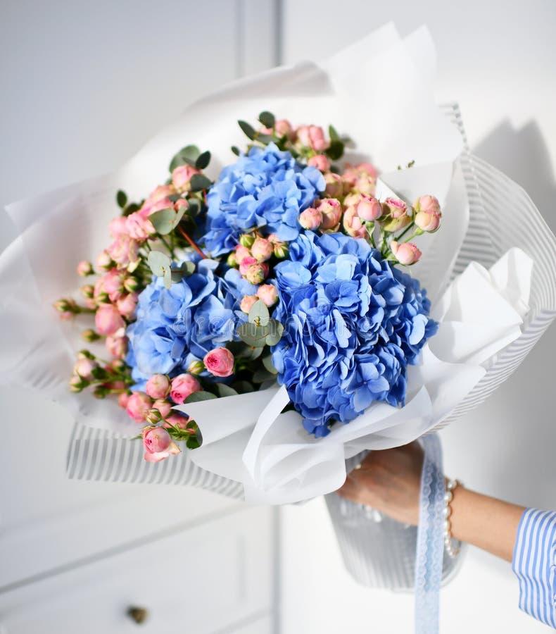 Frauenhandgriffblumenstrauß von blauen Hortensieblumen und von rosa Rosen stockfotografie
