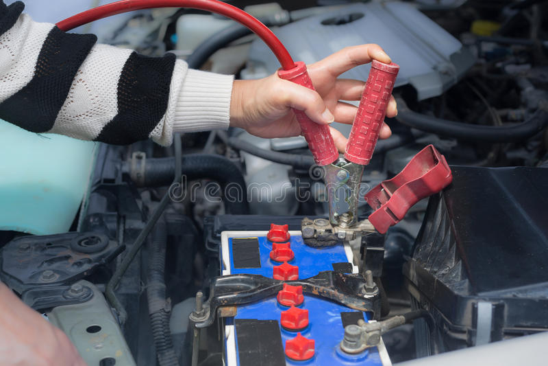 Frauenhandgriffstarthilfekabel zur Autobatterie stockbild