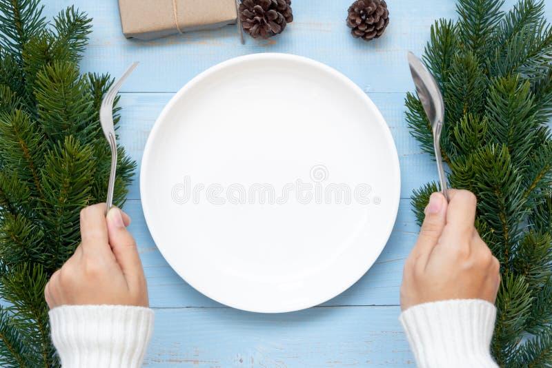 Frauenhandholding Löffel und Gabel über leerer Platte mit Weihnachtsdekoration, Vorbereitung für guten Rutsch ins Neue Jahr und W stockfotos