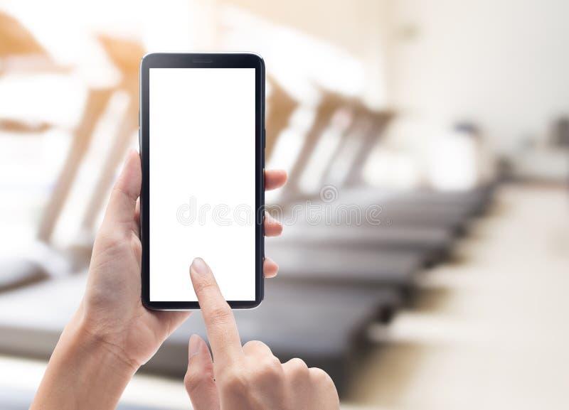 Frauenhandholding und Berühren des schwarzen Smartphone mit Modellschablone des leeren Bildschirms für Ihren Entwurf auf abstrakt stockbilder