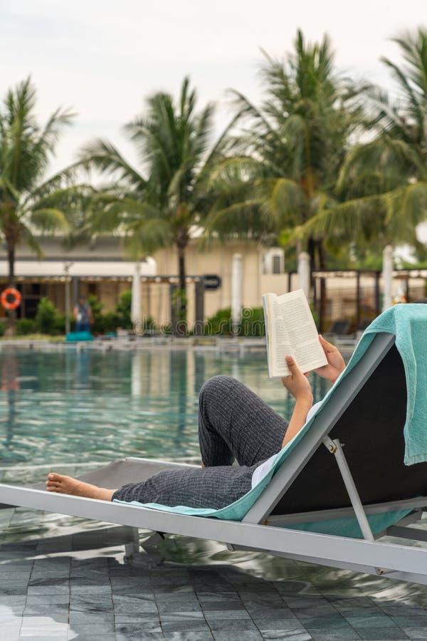 Frauenhandholdingbuch beim Ablesen am Swimmingpool stockbilder