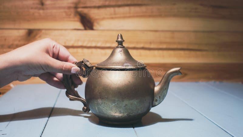 Frauenhandholdinggriff des Weinlesekupfer-Teekannenkessels mit Verunstaltungen und Kennzeichen, Sitzen im blauen Holztisch lizenzfreie stockfotografie