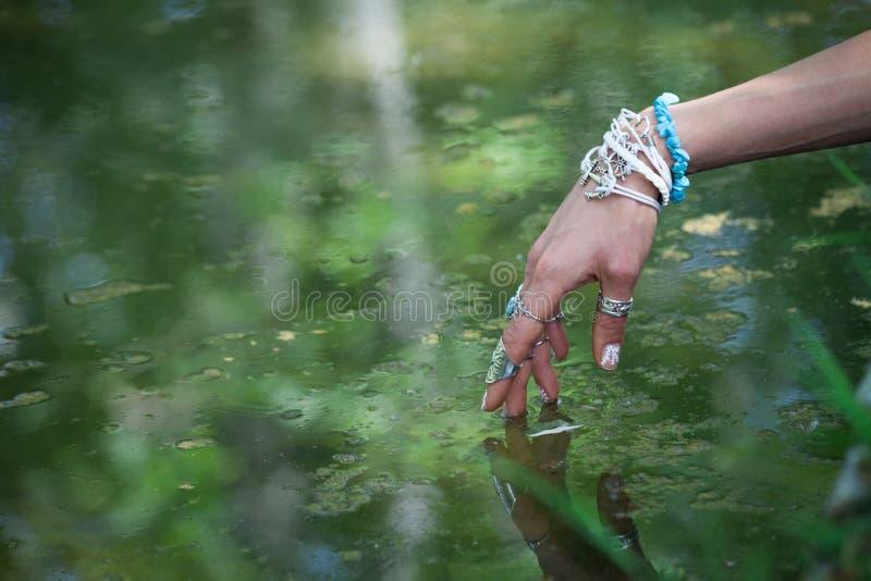 Frauenhandrührendes Wasser mit boho Art schellt und Armbanden lizenzfreie stockbilder