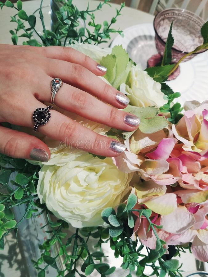 Frauenhandromantisches Foto der silbernen metallischen Maniküregel-Nagellack-Musterschönheitsmode-Blume stockfotografie