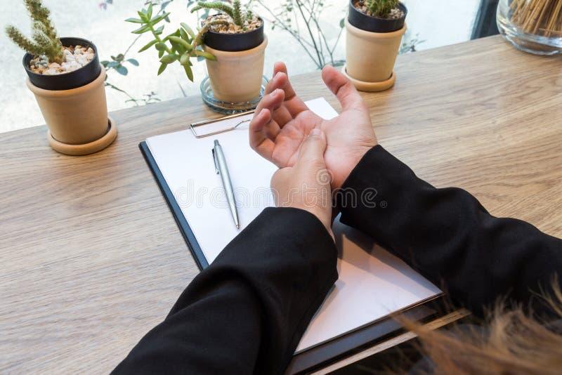 Frauenhandschmerz auf Schreibtisch - Bürosyndrom lizenzfreies stockbild