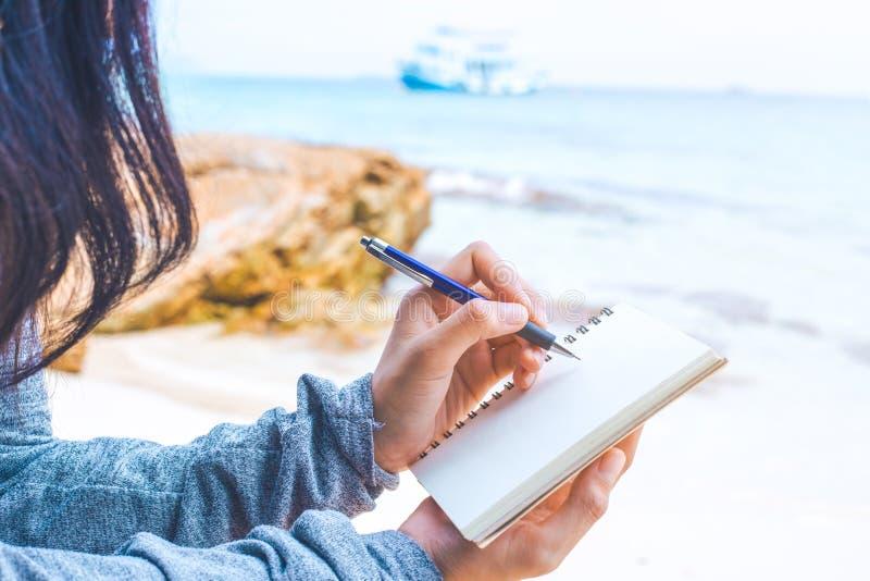 Frauenhandschrift auf einem Notizblock mit einem Stift am Strand lizenzfreie stockfotografie