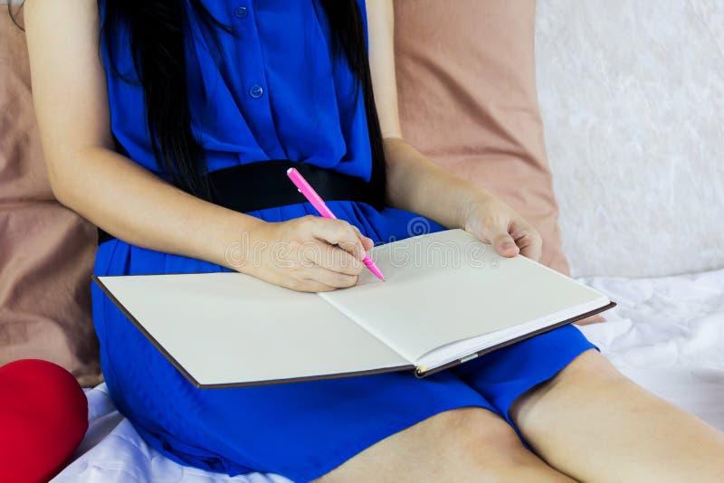 Frauenhandschrift unten auf leerem Arbeitsbuch oder Broschüre lizenzfreie stockfotografie