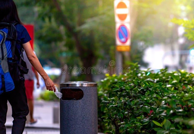 Frauenhandwerfende verdrehte leere Wasserflasche im Papierkorb Grauer Plastikpapierkorb Wandererausschussflasche im Abfalleimer stockbild