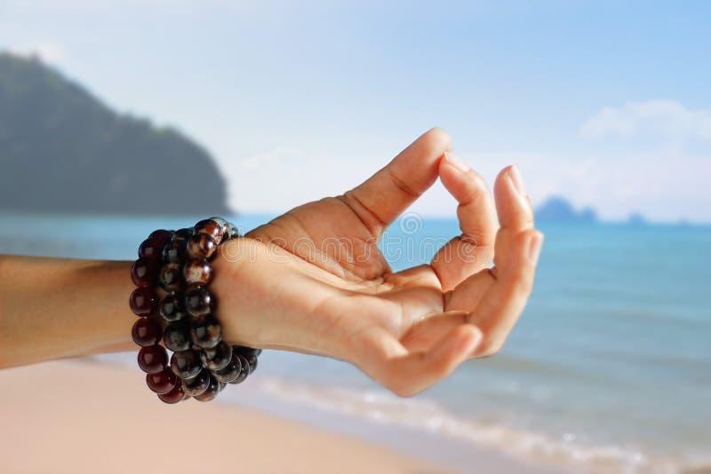 Frauenhandyoga und -meditation auf dem Sommer setzen Hintergrund auf den Strand lizenzfreie stockbilder