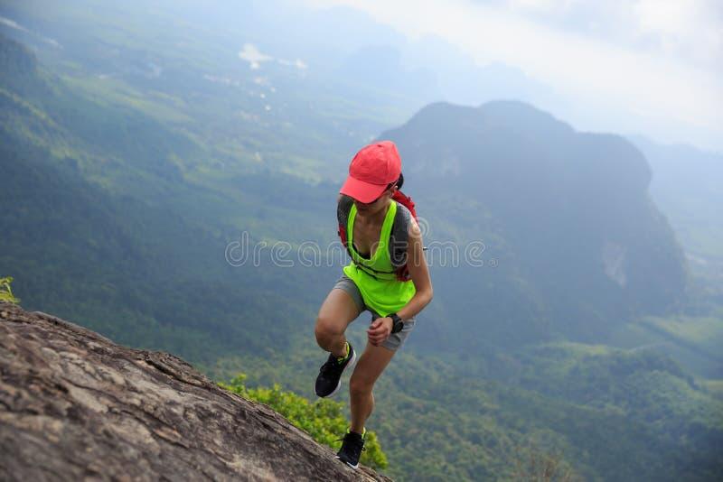 Frauenhinterläufer, der an der Gebirgsspitze läuft lizenzfreie stockfotos