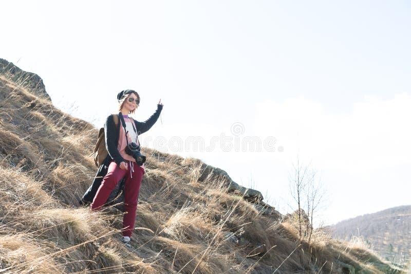 Frauenhippie-Fotograf mit dslr Kamera Stilvolles Mädchen, das in der Sonnenbrille mit einer Kamera auf der Naturvertretungshand l stockfotografie