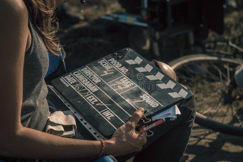 Frauenholding clapperboard draußen stockbilder
