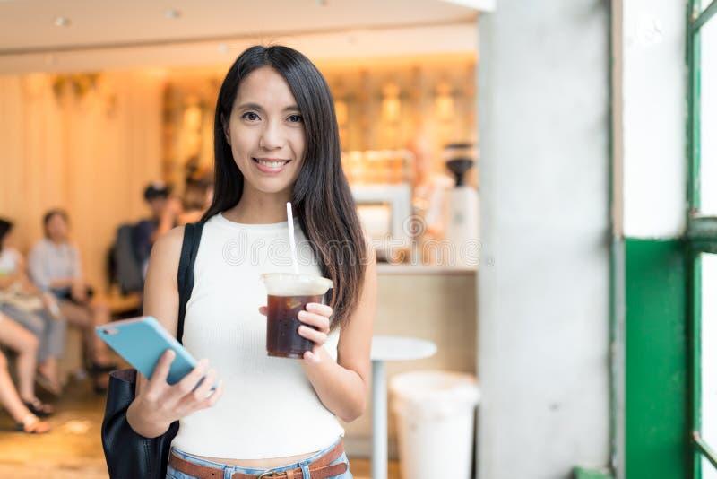Frauenholding gefror Kaffee und Mobiltelefon lizenzfreies stockbild
