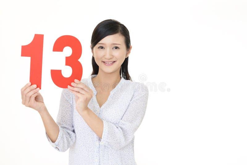 Frauenholding Nr. dreizehn lizenzfreie stockbilder