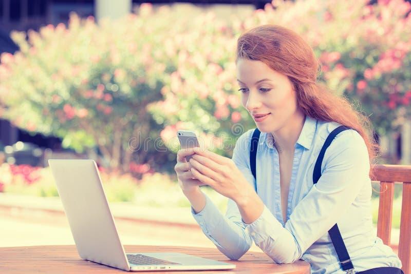 Frauenholding, unter Verwendung intelligenten, des Handys und des Computers lizenzfreies stockbild