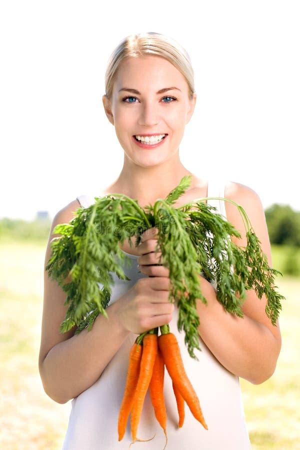 Frauenholdingbündel Karotten lizenzfreie stockfotos