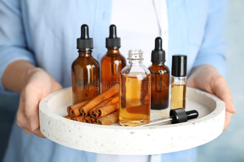 Frauenholdingbehälter mit verschiedenen Flaschen ätherischen Ölen lizenzfreie stockfotos