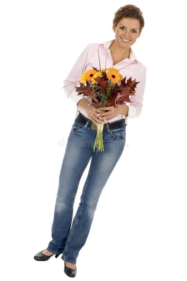 Frauenholdingblumenstrauß stockbild