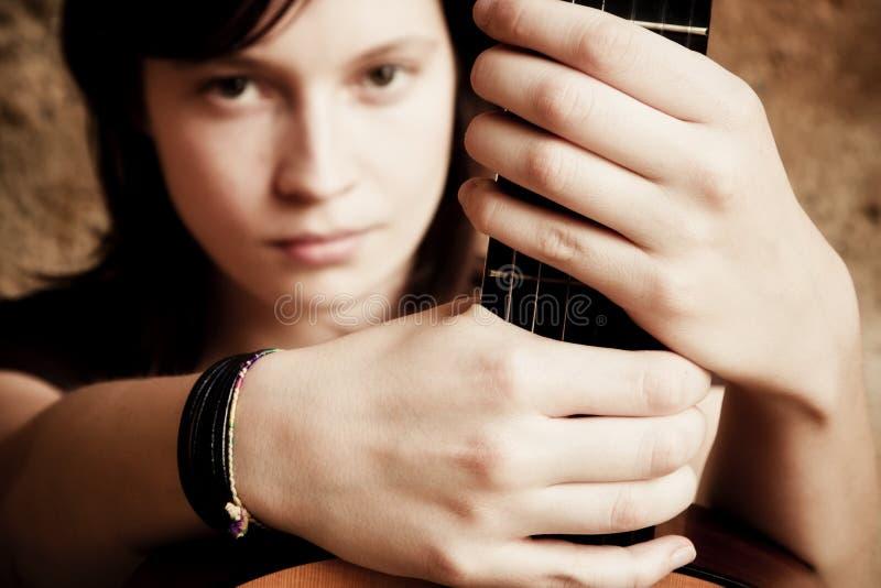 Frauenholdinggitarre stockbild