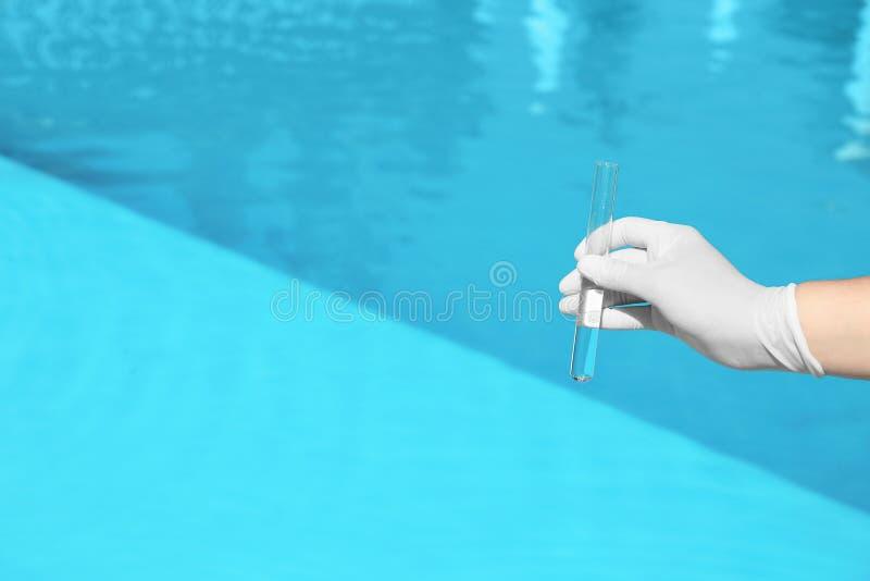 Frauenholdingglasrohr mit Probe des Swimmingpoolwassers, zum des pH-Niveaufreiens, Nahaufnahme zu überprüfen stockbild