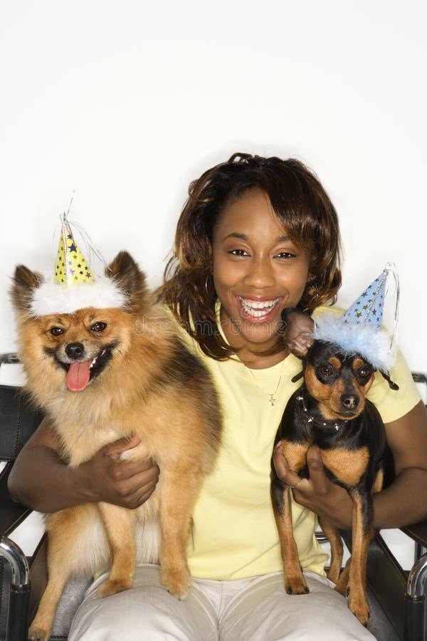 Frauenholdinghunde, die Partyhüte tragen. stockbild