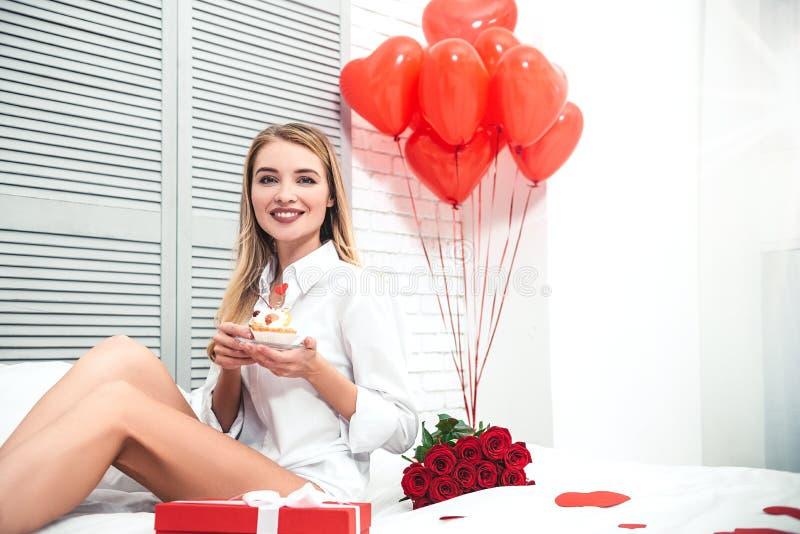 Frauenholdingkleiner kuchen mit Geschenken auf dem Bett stockbild