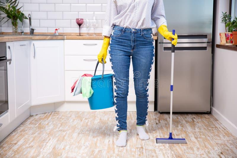 Frauenholdingmop und -eimer mit Reinigungsmitteln zu Hause stockfoto