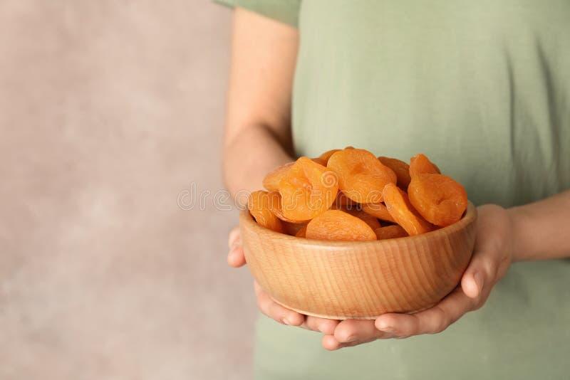 Frauenholdingschüssel mit getrockneten Aprikosen auf Farbhintergrund, Raum für Text stockfotografie