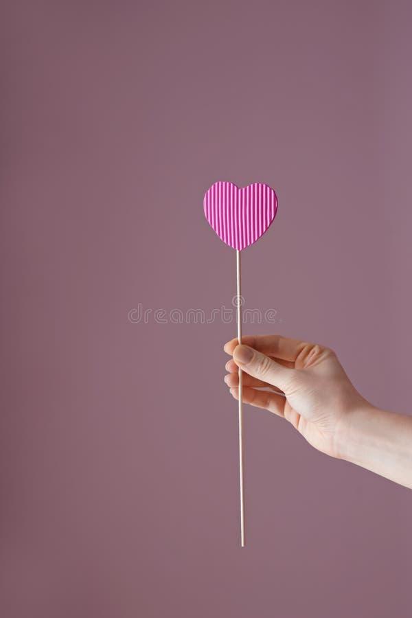 Frauenholdingstock mit Papierherzen auf Farbhintergrund lizenzfreie stockfotos