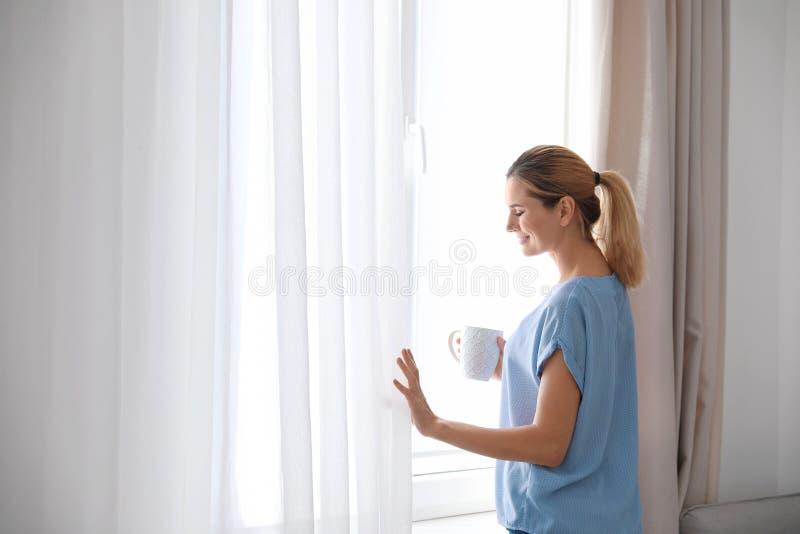 Frauenholdingtasse kaffee nahe Fenster mit schönen Vorhängen zu Hause lizenzfreies stockfoto